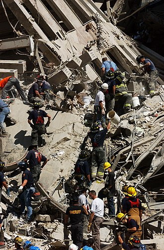 "Rescue and recovery effort after the September 11 attacks on the World Trade Center - A ""bucket brigade"" works to clear rubble and debris on September 14, 2001"