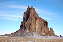 Solid rock spire protruding from the desert.