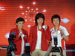 Wang Yuegu - Wang (left) with her women's table tennis teammates Li Jiawei and Feng Tianwei showing off their silver medals won at the 2008 Summer Olympics during a ceremony on 25 August 2008 to welcome Team Singapore home