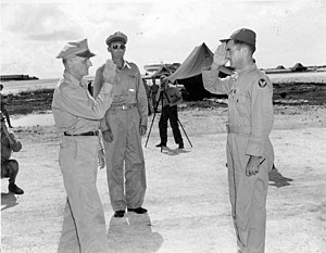 A man in a flight suit and peaked cap exchanges salutes with a man in uniform. Multiple photographers capture the moment.