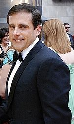 A man with black hair, Steve Carell, is standing in a tux. He is looking towards, but not directly at, the camera.
