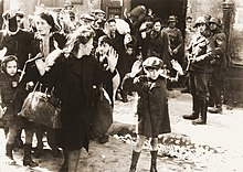 Iconic photograph of Jewish women and children being herded out of a building