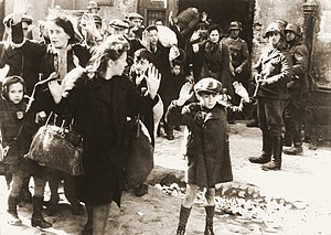 Dehumanization - In this famous image from the Warsaw Ghetto Uprising, Josef Blösche (far right) and other Nazi soldiers gather up Jewish people for persecution.