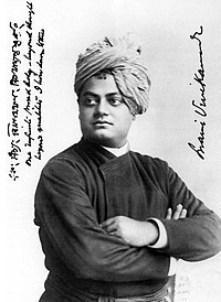"A black and white photo of a man, pictured from his waist up. The man stands with folded arms, wearing a dark full sleeve shirt and a turban. On the photo, in Sanskrit (in Bengali script), and in English: ""One infinite pure and holy—beyond thought beyond qualities I bow down to thee"" is written - signed Swami Vivekananda"
