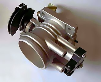 Throttle - Throttle body showing throttle position sensor. The throttle cable attaches to the curved, black portion on the left. The copper-coloured coil visible next to this returns the throttle to its idle (closed) position when the pedal is released.