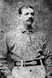 A man standing in his baseball uniform.