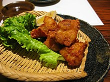 Japanese-style fried chicken on a plate alongside some lettuce
