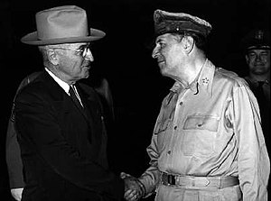 Truman in a dark suit and tie and light hat shakes hands with MacArthur, in uniform wearing a shirt but no tie and his rumpled peaked cap.