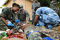 U.S. Army Sgt. Trey Carter, center, a nurse, and combat medic, with 94th Combat Support Hospital works alongside Belize Defence Force medics, on a mock casualty role player, during a medical exchange, at Price 100830-A-CL600-158.jpg