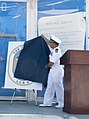 U.S. Navy Cmdr. Mike Davies, center, commanding officer of the littoral combat ship Pre-Commissioning Unit Jackson (LCS 6), reveals the ship's crest during a crest unveiling ceremony at Mariner Park Amphitheater 130827-N-YQ852-043.jpg