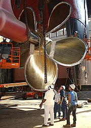 Shipyard employees reattaching the bronze propeller of Washington while in dry dock