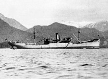 Side view of a ship upon water, with mountains visible in the background