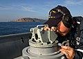 US Navy 021210-N-8029P-003 As Pioneer departs San Diego Bay, Quartermaster 3rd Class Russell Hauck takes visual bearings using an alliade.jpg