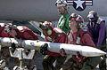 US Navy 030418-N-2385R-011 Aviation Ordnanceman lift an AIM-120 Advanced Medium-Range Air-to-Air Missile (AMRAAM) from its weapon skid to load it onto an F-A-18C Hornet.jpg