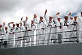 US Navy 060905-N-4965F-007 Sailors assigned to guided missile destroyer USS Russell (DDG 59) wave to friends and family members as the ship returns following a six-month deployment.jpg