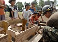 US Navy 070707-N-4267W-008 Local children watch as Steelworker 3rd Class John Smith, with Amphibious Construction Battalion (ACB) 1, constructs new desks for a local school.jpg