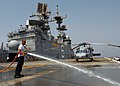 US Navy 070807-N-3211R-004 Aviation Boatswain's Mate (Handling) Airman Lawrence Llorente, a native of Vigan City, Philippines, use a fire hose to wash salt off the flight deck during a fresh water wash down.jpg