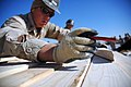 US Navy 080117-N-7367K-002 Builder 3rd Class Shawn Laborde assigned to Naval Mobile Construction Battalion (NMCB) 1, Task Force Sierra, strikes a line on a piece of lumber to be used in the construction of huts.jpg