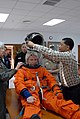 US Navy 081209-N-1825E-013 NASA training team member George Brittingham puts a space suit helmet on Naval Station Rota Nurse Lt. Lisa Steiner.jpg