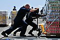 US Navy 090324-N-1488S-030 Ship's Serviceman 2nd Class Nicholas Wilson, left, and Operations Specialist Seaman Apprentice Timothy Green move pallets of soda onto an elevator aboard the Arleigh Burke-class guided-missile destroy.jpg