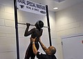 US Navy 100529-N-8689C-519 U.S. Navy SEAL assists a swimmer with pull-ups in the SEAL fitness challenge during the 8th annual National Black Heritage Championship Swim Meet.jpg