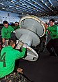 US Navy 100718-N-0569K-126 Sailors assigned to the Air department of the aircraft carrier USS Enterprise (CVN 65) move a spool that holds the number two arresting gear wire.jpg