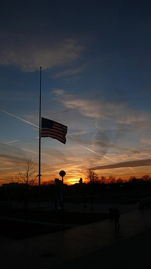 US flag flying at half-staff at sunset