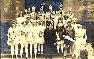 The Whiffenpoofs - Whiffenpoofs of 1912 (dressed in tutus) posing with Louie Linder (in tophat), 1912