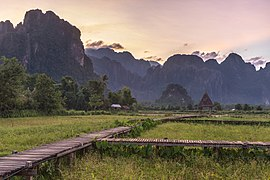 Wooden walkway leading to a hut with straw roof in front of karst mountains at sunset, Vang Vieng, Laos.jpg