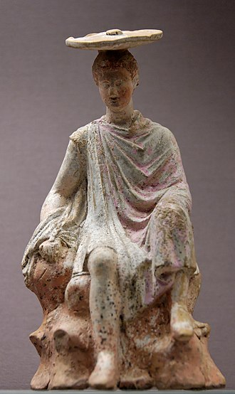 Tanagra figurine - (Tanagra figurine) A young man seated on a rock. Back roughly modelled; square vent. Red on hair and boots; orange-pink on rock; pink on skin; rose-madder with blue border on cloak. British Museum 1874