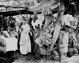 Roman Catholic Archdiocese for the Military Services, USA - A US Navy chaplain celebrates Catholic Mass for Marines at Saipan, June 1944, commemorating comrades fallen in initial amphibious landings.