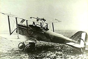 Side view of military biplane with pilot in cockpit, parked on an airfield