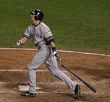 A man wearing a gray baseball uniform and navy-blue helmet drops his black baseball bat behind him after a swing.