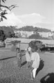 ASC Leiden - NSAG - van Es 2 - 006 - Two boys and a naked girl with an umbilical hernia on a lawn in front of new barns - Kampala, Uganda - 29-11-1961 - 4-12-1961.tiff