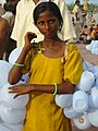 A girl selling plastic containers for carrying Ganges water, Haridwar.jpg