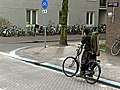 A girl with violin on her back, mobile phoning, in Amsterdam city, 2013.jpg