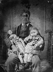 A man holding a child and a doll