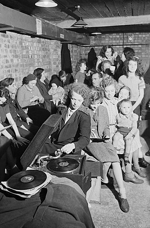 History of DJing - A young woman plays a gramophone in an air raid shelter in north London (1940).