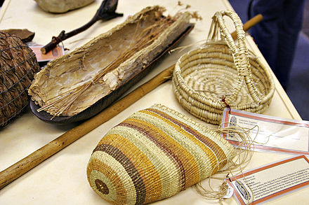 Aboriginal women's implements, including a coolamon lined with paperbark and a digging stick. This woven basket style is from Northern Australia. Baskets were used for collecting fruits, corms, seeds and even water – some baskets were woven so tightly as to be watertight. Aboriginal craft made from weaving grass.jpg