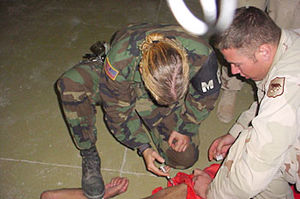Abu Ghraib prison - US Military Police officer restraining and sedating a prisoner, while a soldier holds him down