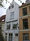 foto van De drie gekroonde suikerbroden: huis met hoogopgaande gepleisterde tuitgevel, in een gebeeldhouwde gevelsteen gedateerd