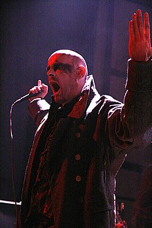Head and upper body shot of a male singer, with a shaved head and blackened eyes, performing on stage. He is wearing a double-breasted military overcoat with a large collar.