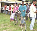 An elderly lady being carried on a bicycle to a polling station of Nowgong Parliamentary of Assam during General Elections 2004 on April 26, 2004.jpg