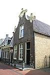 foto van Pand met zolderverdieping en zesruitsvensters onder zadeldak tegen klokgevel met aanzetkrullen en beeldhouwwerk