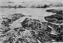 Black and white aerial photo of a body of water surrounded by steep snow-topped mountains. Several ships are anchored in a bay, with the battleship Tirpitz's location being marked with an arrow.