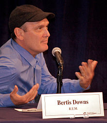 Bertis Downs looking to the camera's left and gesturing with his hands as he sits at a table behind a placard with his name