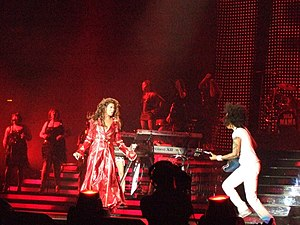 "The Beyoncé Experience - Knowles performing ""Ring the Alarm"" in May 2007. During a performance of the song in Orlando, Florida on July 24, she fell down a flight of stairs as her long red coat got caught under her heel."