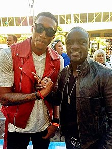Two black men pose for the camera. The left man is taller and bends slightly to the right in order to fit into view. He wears black sunglasses, a white t-shirt with a red vest, and black pants. He has his right hand clasped in a gesture with the right hand of the man on the right, who makes a peace symbol gesture with two fingers of his right hand. The man on the right wears a black leather jacket over a black shirt, a silver-colored necklace, and blue jeans with a studded belt.