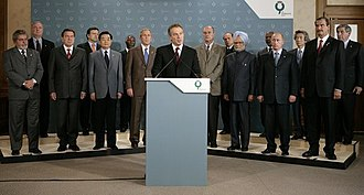 31st G8 summit - UK Prime Minister Tony Blair speaks with the summit attendees behind him. Left to right (front row): Lula da Silva, Gerhard Schröder, Hu Jintao, George W. Bush, Tony Blair at podium, Jacques Chirac, Manmohan Singh, Vladimir Putin, Vicente Fox; (back row): Paul Martin, José Barroso, Thabo Mbeki, Silvio Berlusconi, Kofi Annan, Junichiro Koizumi and Paul Wolfowitz.