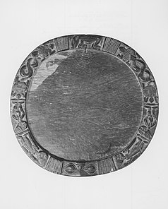 A roughly circular wooden tray with a raised border carved with human and animal figures.